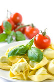 Tortellini. Served on a plate with basil leaves and tomatoes stock photos