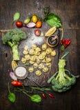 Tortellini avec les légumes frais, préparation avec de la farine sur le fond en bois rustique, vue supérieure photographie stock