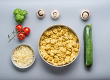 Tortellini bowl with zucchini, mushrooms and vegetarian cooking ingredients on kitchen table background with cutting board , top v. Iew, flat lay. Healthy Stock Images