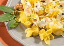 Tortellini casalinghi italiani con il salmone, la crema, il pepe nero e le noci Immagini Stock