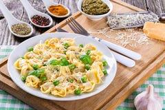 Tortellini com ervilhas verdes, pinhões, queijo parmesão e ralador Imagem de Stock