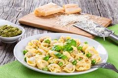 Tortellini com ervilhas verdes, pinhões, queijo parmesão e ralador fotos de stock
