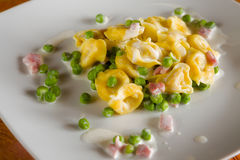 Tortellini with cream ham and peas Stock Photo