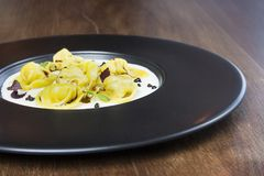 Tortellini in a creamy parmesan sauce. Hand made typical italian pasta named named tortellini on a black plate on a wood table Stock Images
