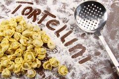 Tortellini e utensílio frescos com farinha na tabela Fotografia de Stock