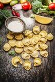 Tortellini fait maison frais avec les ingrédients et la farine de légumes sur le fond en bois foncé Images libres de droits