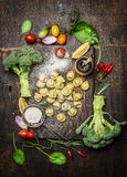 Tortellini with fresh vegetables , preparation with flour on rustic wooden background, top view. Stock Photography