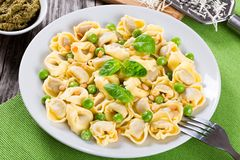 Tortellini with green peas, fried Pine nuts,  top view Stock Photography