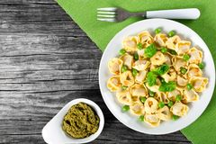 Tortellini with green peas, fried Pine nuts,  top view Stock Images