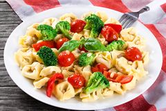 Tortellini with grilled cherry tomatoes, broccoli, red bell pepper, top view Royalty Free Stock Images