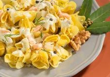 Tortellini hecho en casa italiano con los salmones, la crema, las nueces y la hoja de laurel Imágenes de archivo libres de regalías