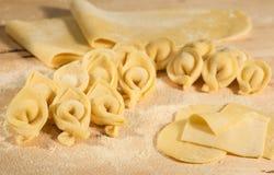 Tortellini hecho en casa italiano y pasta hecha a mano cruda, colocados en la tabla de madera y asperjados con la harina Fotos de archivo