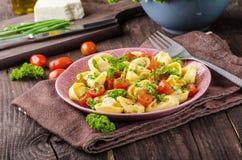 Tortellini llenado con las hierbas, tomates Imagen de archivo