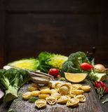 Tortellini  Making with vegetales ingredients on rustic kitchen table over dark wooden background Stock Photography