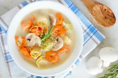 Tortellini and mushroom soup, overhead on a marble background Royalty Free Stock Images