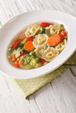 Tortellini soup with broccoli, peas, carrot and pepper close-up. Stock Photography