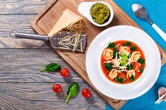 Tortellini soup with italian sausages, spinach, tomato, parmesan cheese , pesto-sauce Royalty Free Stock Images
