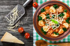Tortellini soup with italian sausages, spinach, tomato, parmesan cheese , top-view Royalty Free Stock Photography