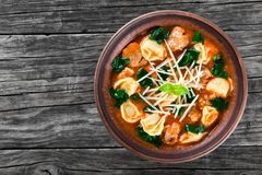 Tortellini soup with italian sausages, spinach, tomato, parmesan cheese , top-view Stock Image