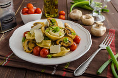 Tortellini stuffed with a mixture of vegetable spring. Homemade tortellini stuffed with mushrooms and spring onion, roasted tomatoes, garlic souce, topped royalty free stock images