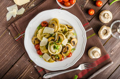 Tortellini stuffed with a mixture of vegetable spring. Homemade tortellini stuffed with mushrooms and spring onion, roasted tomatoes, garlic souce, topped stock images