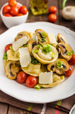 Tortellini stuffed with a mixture of vegetable spring. Homemade tortellini stuffed with mushrooms and spring onion, roasted tomatoes, garlic souce, topped stock photos