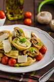 Tortellini stuffed with a mixture of vegetable spring. Homemade tortellini stuffed with mushrooms and spring onion, roasted tomatoes, garlic souce, topped royalty free stock photo