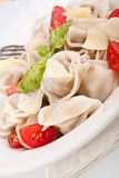 Tortellini with tomatoes and basil Stock Photo