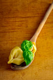 Tortellini on wooden spoon Stock Photos