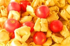 Tortellini y fondo de los tomates Imagen de archivo libre de regalías