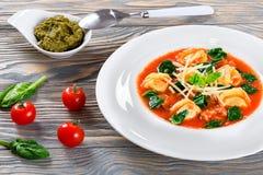 Tortellinisoep met Italiaanse worsten, spinazie, tomaat, parmezaanse kaaskaas, pesto-saus royalty-vrije stock afbeeldingen