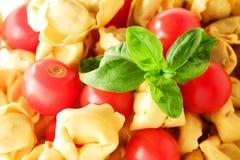 Tortelliniteigwaren, Tomaten und Basilikumhintergrund Lizenzfreies Stockfoto