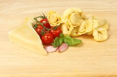 Tortelloni and ingredients. Tortelloni with garlic,basil,tomatoes and pecorino cheese on a wooden chopping board Stock Photos