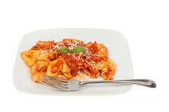 Tortelloni pasta on a plate. With a fork isolated against white Stock Photo