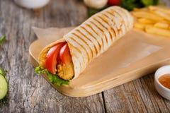 Tortiglia con il pollo e pomodori su un supporto di legno Immagini Stock Libere da Diritti