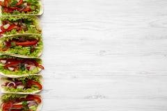 Tortilhas de milho com avermelhado, pepino da vista superior, cebola, salsa, p foto de stock