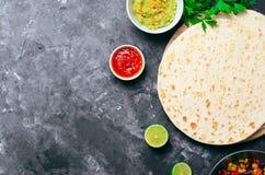 Tortilhas lisas com salsa do tomate, Guacamole e salsa fresca no fundo escuro, tortilhas do trigo, alimento mexicano imagens de stock