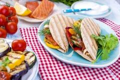 Tortilla με τα λαχανικά και σολομός στα αρσενικά χέρια ικανότητα σιτηρεσίου δημ&e υγιές μεσημεριανό γεύμα Λαχανικά και ψάρια, Στοκ Εικόνες