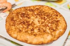 Tortilla av potatisen på den vita plattan på tabellen arkivbild