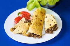 Tortilla avec du boeuf haché sur le fond bleu Image stock