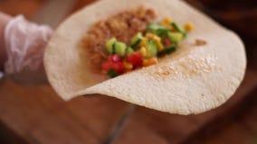 Tortilla avec un mélange des ingrédients clips vidéos