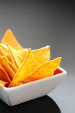 Tortilla Chips. Some cheese flavored tortilla/Nacho chips in a bowl on dark background Royalty Free Stock Photography