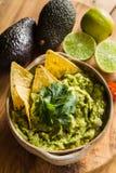 Tortilla-Chips in der Schüssel Guacamolen mit Avocado und Kalken Lizenzfreie Stockfotografie
