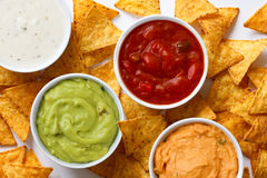 Tortilla chips and dips. Four white round ceramic bowls with mixed dips from above with tortilla chips scattered around stock images