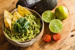 Tortilla-Chips in einer Schüssel Guacamolen tauchen mit Avocadokalk- und Kirschtomatenbestandteilen ein Stockfoto