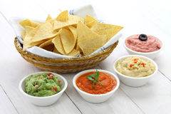 Tortilla chips with four dips. Which are salsa roja, guacamole, taramasalata, and hummus stock photo