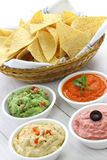 Tortilla chips with four dips. Which are salsa roja, guacamole, taramasalata, and hummus royalty free stock image