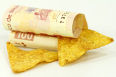 Tortilla chips and pesos. Tortilla chips and mexican pesos on white Royalty Free Stock Photo