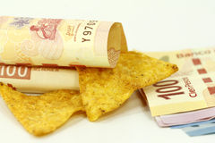 Tortilla chips and pesos. Tortilla chips and mexican pesos on white Royalty Free Stock Image