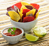 Tortilla chips and salsa. Bowl of salsa with colorful tortilla chips and lime Royalty Free Stock Photos